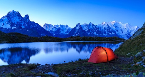 Red tent at Lac De Chéserys in the mountains near Chamonix during sunrise.