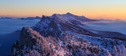 Snow covered Vercors mountains during a winter sunset.