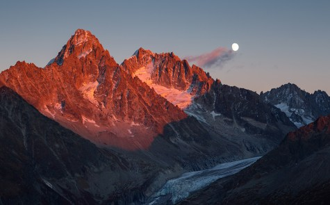 The last sunlight on mountain peak Aiguille D'Argentiere during moonrise. Chamonix, France.