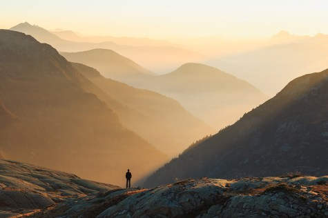 Man looking at the coulorful layers of mountains during sunset.