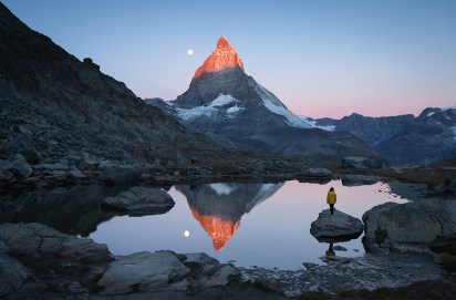 A girl on a rock in the Riffelsee watching the first sunlight shining on the Matterhorn.