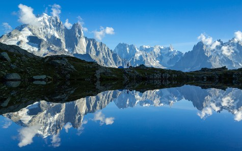 Hiker at his tent and the Mont Blanc massif reflected in Lac de Chesery.