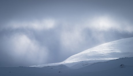 Sunlight shining through the cloudcover over the snow covered mountains in Sarek.