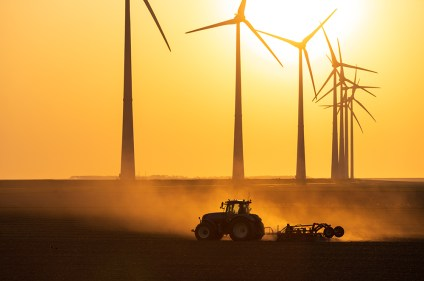 Tractor cultivating farmland during sunset at a row of windturbines producing sustainable energy.