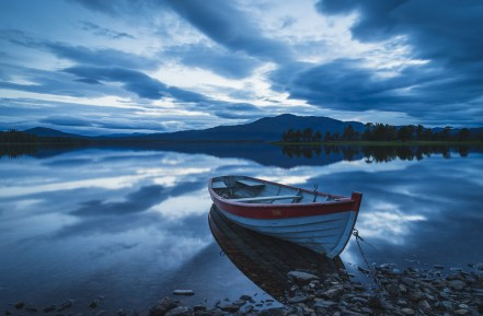 Old rowboat at the rocky shore of a lake on a cloudy evening. Jamtland.