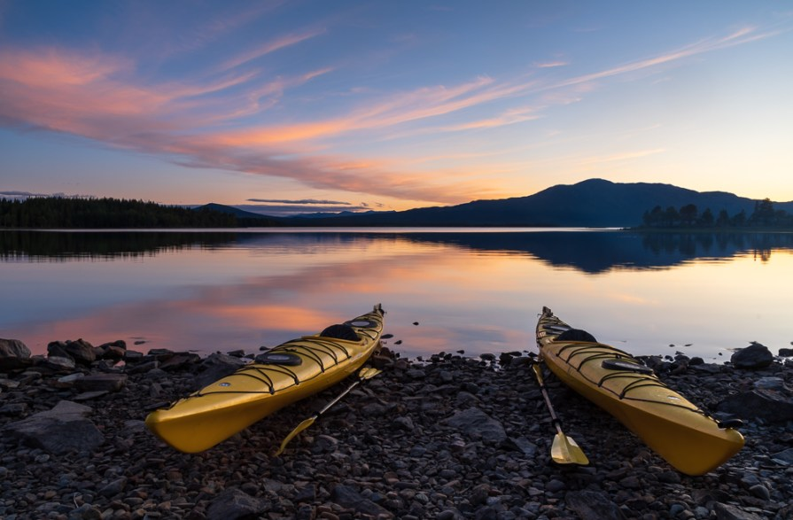 Two kayaks on the shore of a lake during a tranquil dusk. Jamtland.
