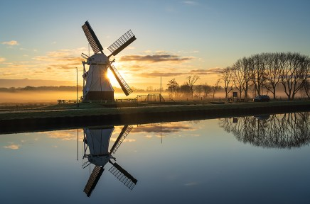 Foggy, winters sunrise at a windmill reflected in a canal.