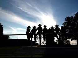 People on farm with cowboy hats & lasso