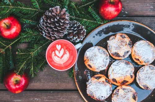 Christmas Marketing Ideas for Small Business – Mince pies on a festive decorated table with pine cones, apples and a hot beverage
