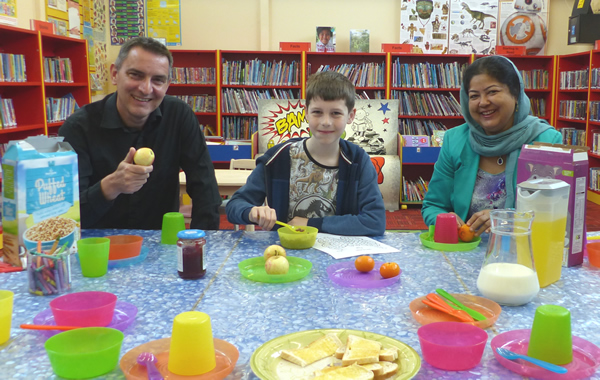 Cllr Hackett, Oliver and Cllr Khatun having breakfast at the library