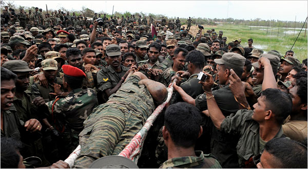 A body identified as that of the Tamil rebels' leader, Vellupillai Prabhakaran, was carried Tuesday through Sri Lankan troops. [Reuter photo: New York Times, May 20, 2009]