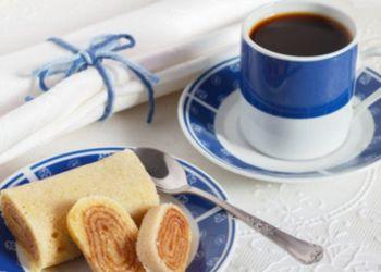 Bolo de rolo (swiss roll, roll cake) typical Brazilian dessert blue cup of coffee. Selective focus