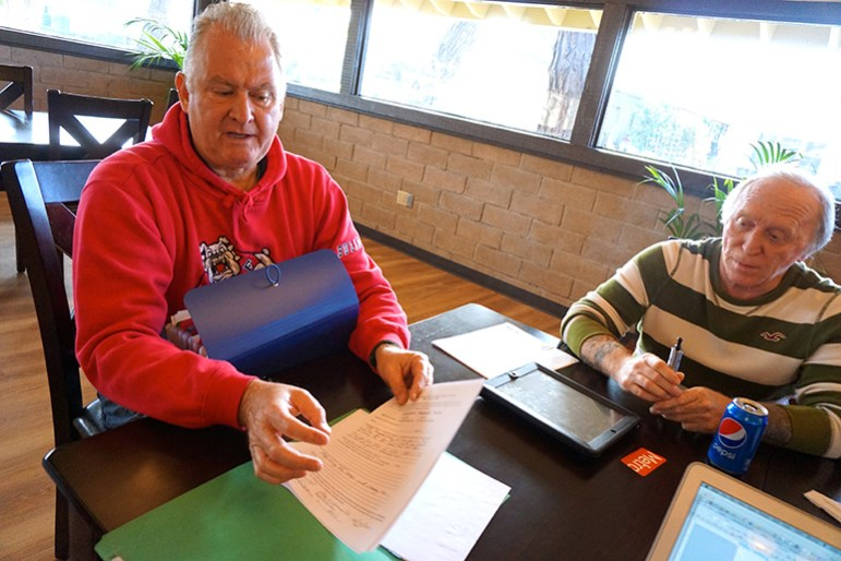 Oak Crest residents Alan Hinman and JJ Vogle sort through records they say show how badly the park fell into disrepair. (Photo by Jennifer Wadsworth)