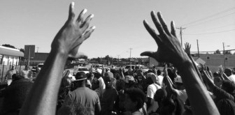 "Protests across the nation have brought attention to how unarmed African-American men are being targeted by law enforcement. Many have used the phrase ""hands up, don't shoot"" as a rallying cry. (Photo by Trymaine Lee, via Twitter)"
