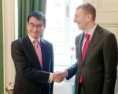 外遊中はラトビアのリンケービッチ外相(右)とも会談し、握手する河野太郎外相=17日、ドイツ・ミュンヘン(共同)