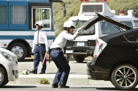 広島県尾道市の向島を出る車両を検問する警察官=21日午後