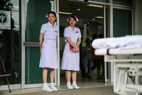 8日、少年らが救出後に搬送されるとみられる病院の外に立つ看護師=タイ北部チェンライ(ゲッティ=共同)