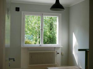 Nymålat rum utan möbler, färgen på väggen är ljust grågrön