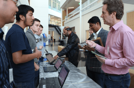 During the judging, Hackathon students Uriel Antonio and Andre Borner answered a technical question from Professor Glenn Bruns as Dean Shyam Kamath (in headset) tested the app, with Professor Sumadhur Shakya and Dean Marsha Moroh looking on. (Credit: Jan Janes Media)