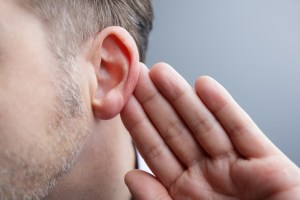 Man with hand on ear listening