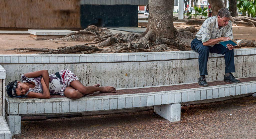 Una persona disagiata dorme su una panchina nella noncuranza di chi le sta accanto