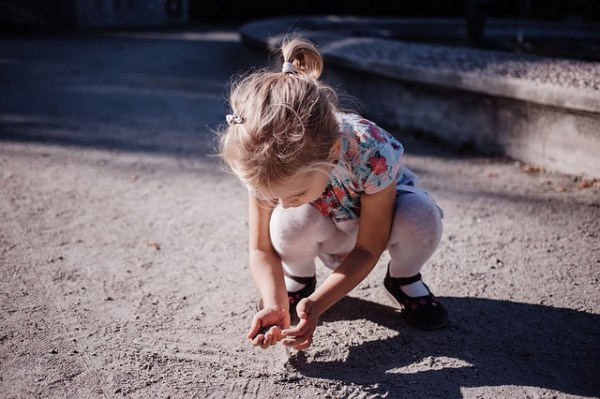 Una bambina si sporca le mani con la terra