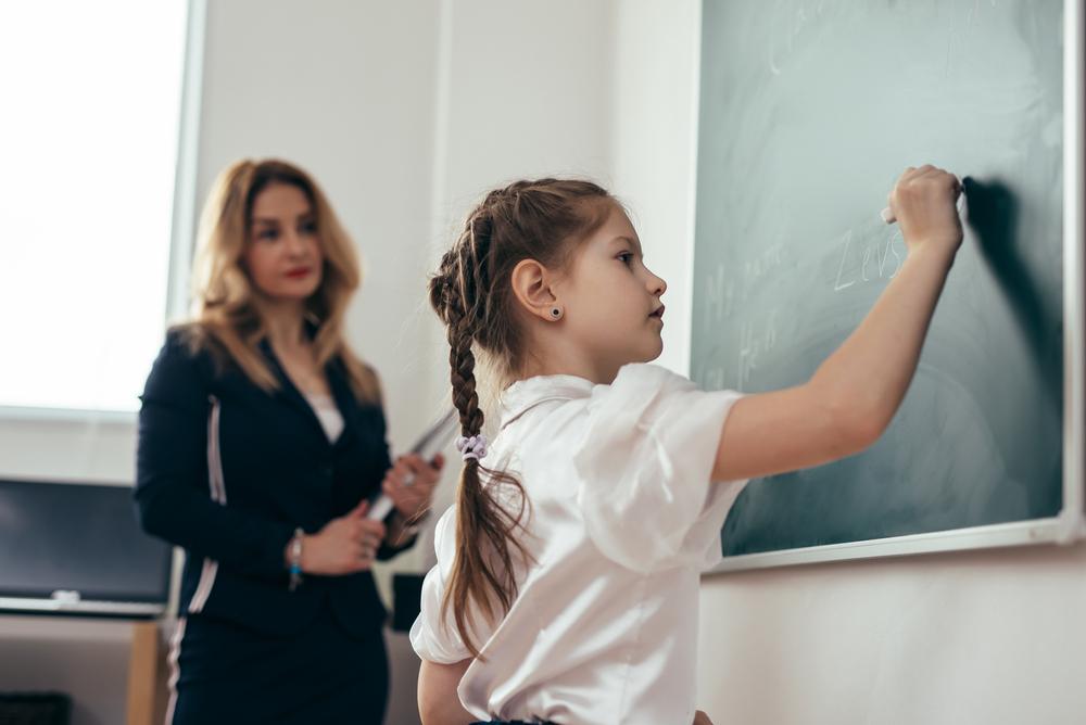 Una bambina di scuola primaria alla lavagna