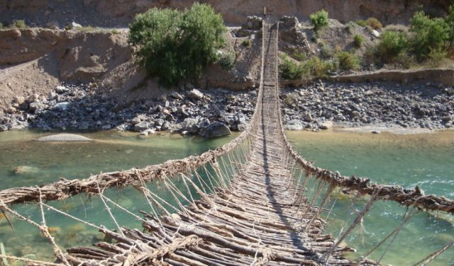 A woven rope bridge extends out over a river to the other side.