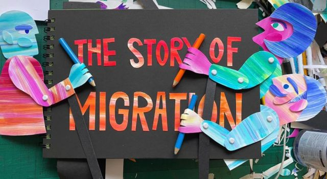 """Three colorful figures made of paper hold colored pencils and stand around a black book called """"The Story of Migration."""" A drafting table covered in scraps of paper fills the background."""