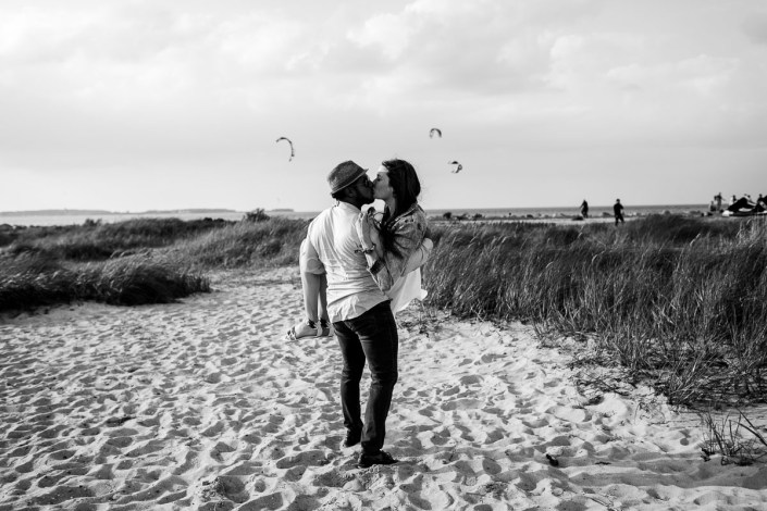 Mann trägt Frau Strand Kuss Kitesurfer