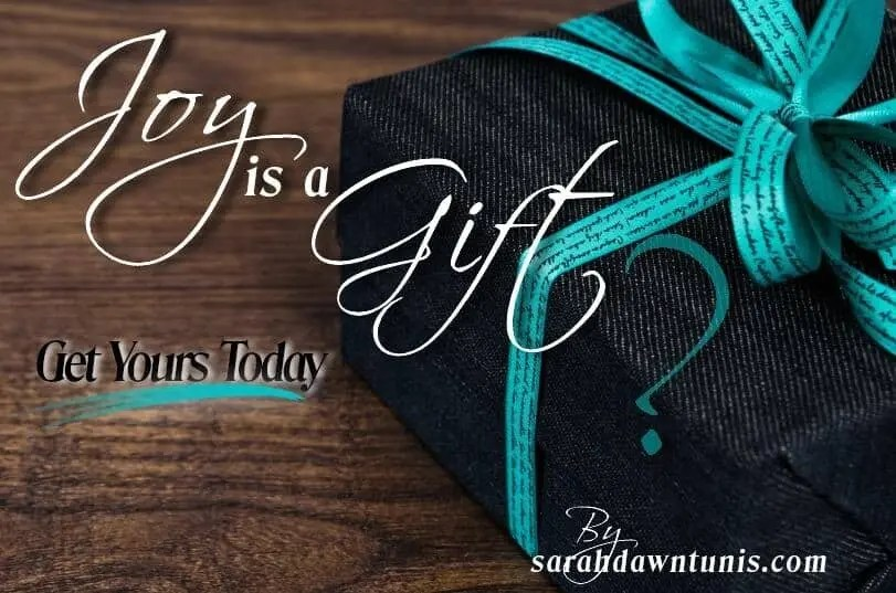 Joy is a Gift word written over a present with a large question mark.