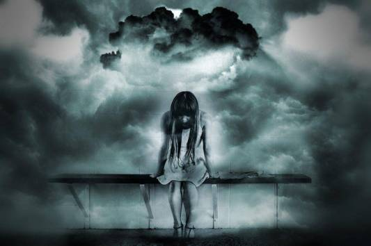 Girl on a bench surrounded by dark clouds. The Angel Number 6 is a message that you are too worried about material matters and need to change your focus.