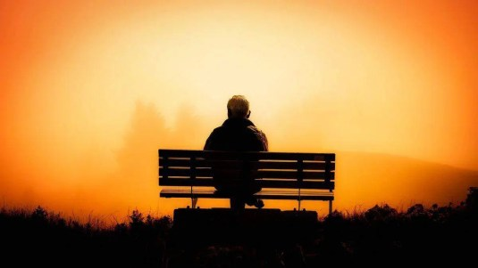 Man sitting on a bench at sunset. The Angel Number 11 is a call to check yourself. Where are your thoughts, feelings and behaviors leading you?