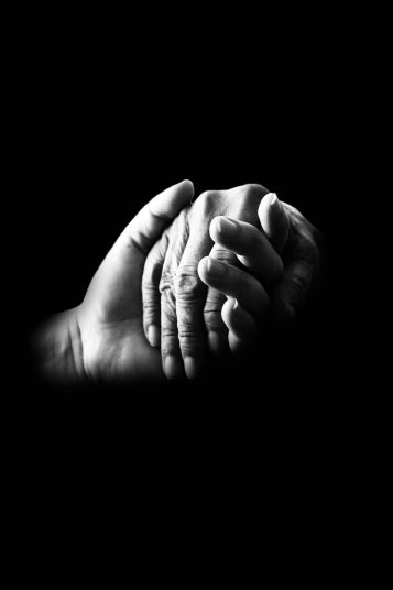 Two hands being held in comfort to represent the peace and comfort you feel when you know the angels