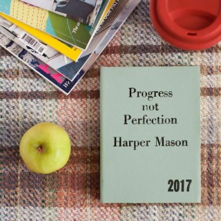 """A book on a table titled """"Progress Not Perfection"""" by Harper Mason representing the angel number 33 reminding you to see you are already doing things right but your need for perfectionism is getting in the way."""