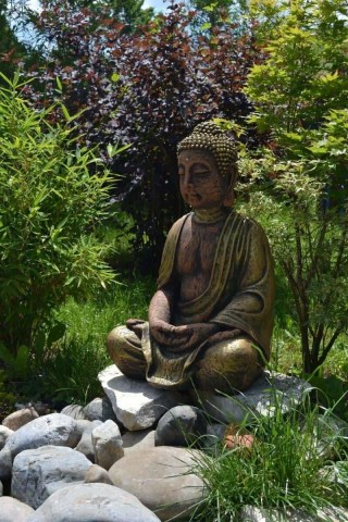 Buddha Statue in a garden representing the angel number 33's meaning that an ascended master is helping you