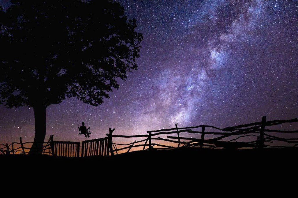 Person on a swing looking at the starry night. Set clear intentions to attract what you want.
