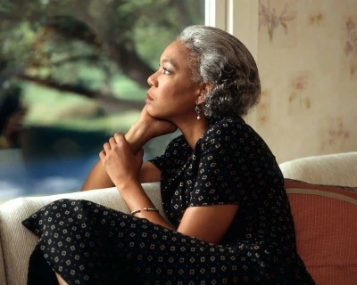 Woman looking out a window. The angel number 1212 is the energy of our power to manifest through our thoughts.