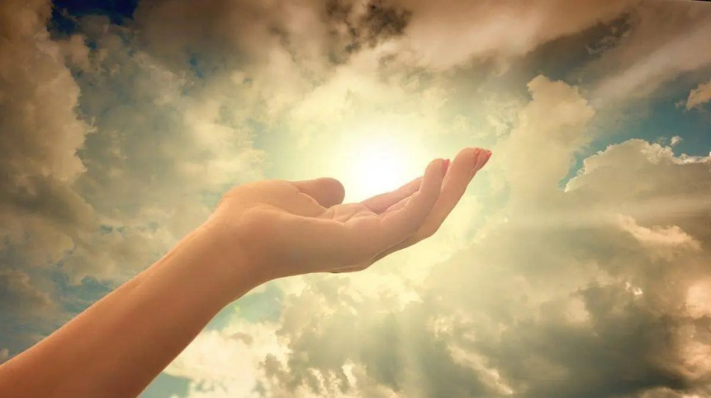 Hand in front of a bright light in the sky. Faith, not giving up, and allowing yourself to receive are important ways to manifest your intentions.