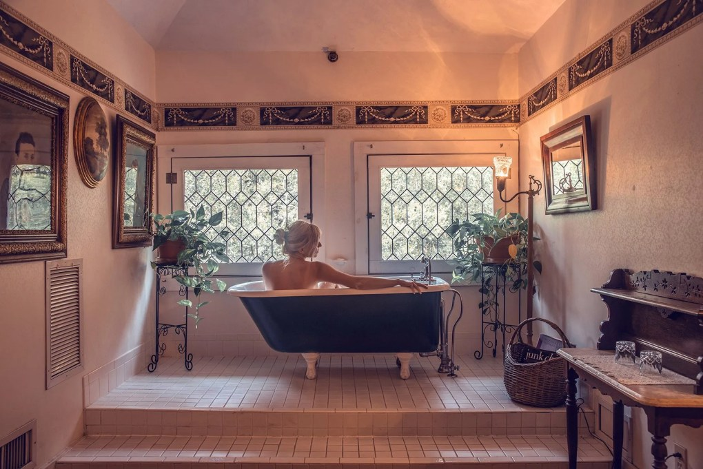 Girl in bath tub in B&B Herlong Mansion