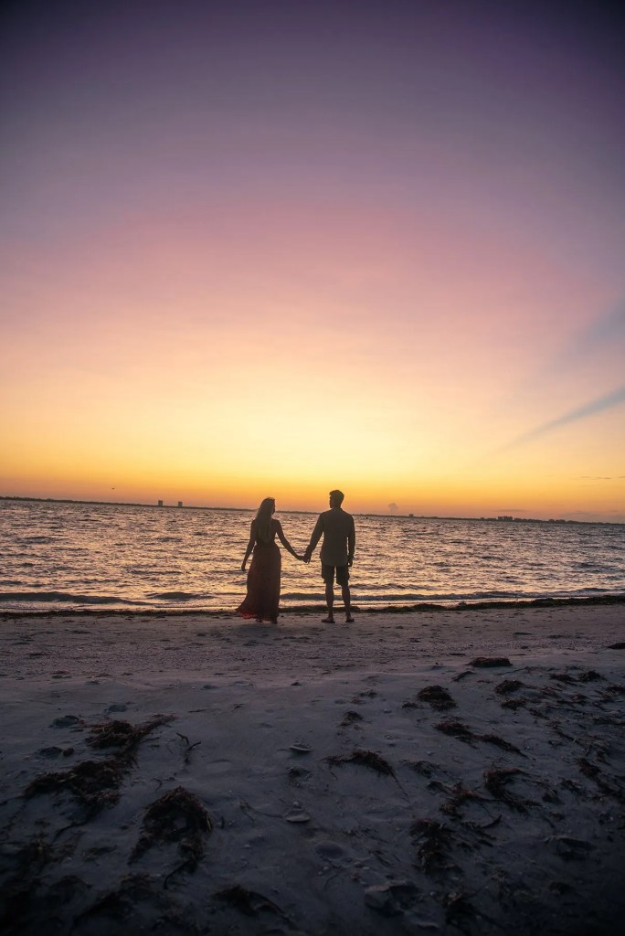 Couple admiring sunrise on beach on Sanibel Island