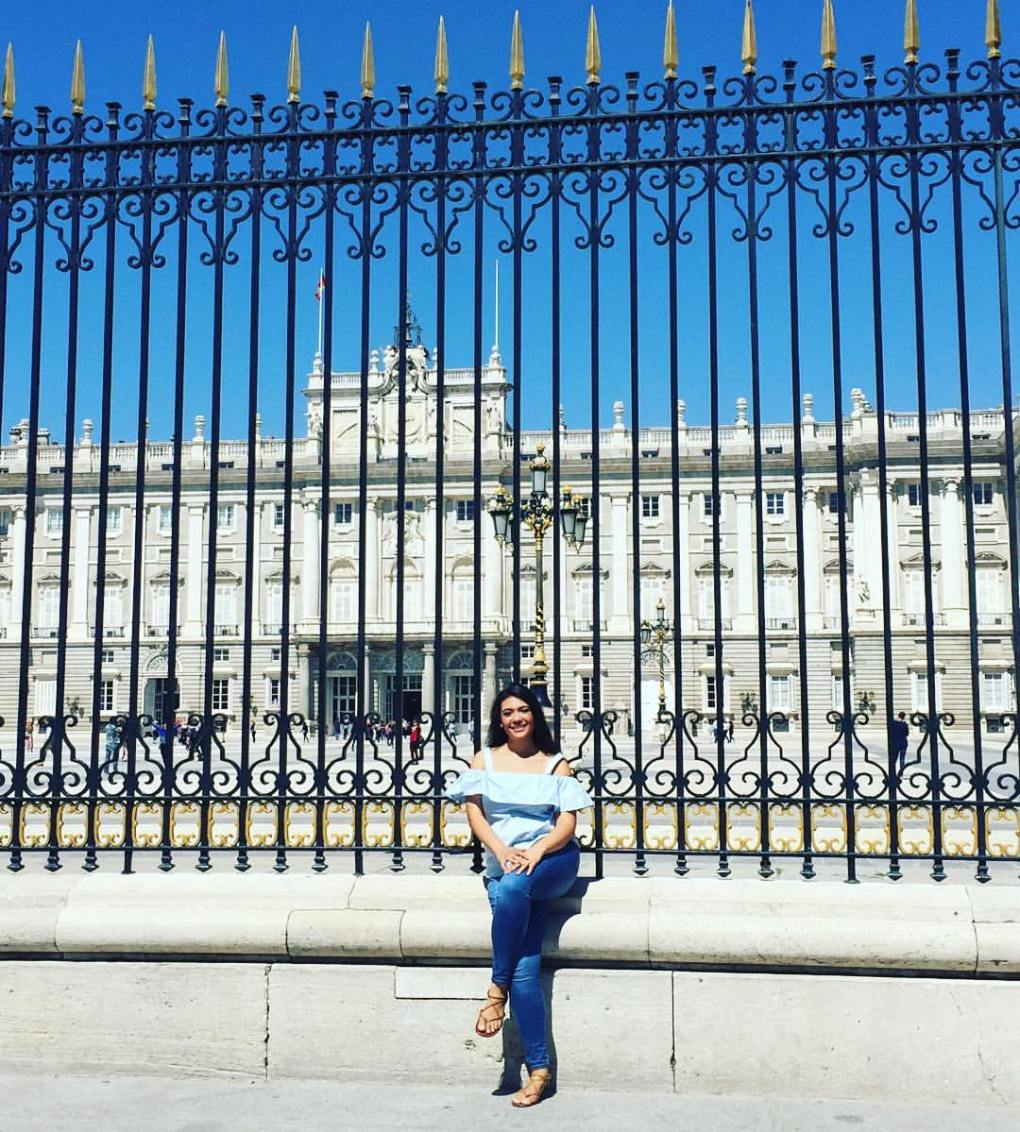 girl sitting in front of the Royal Palace in Madrid