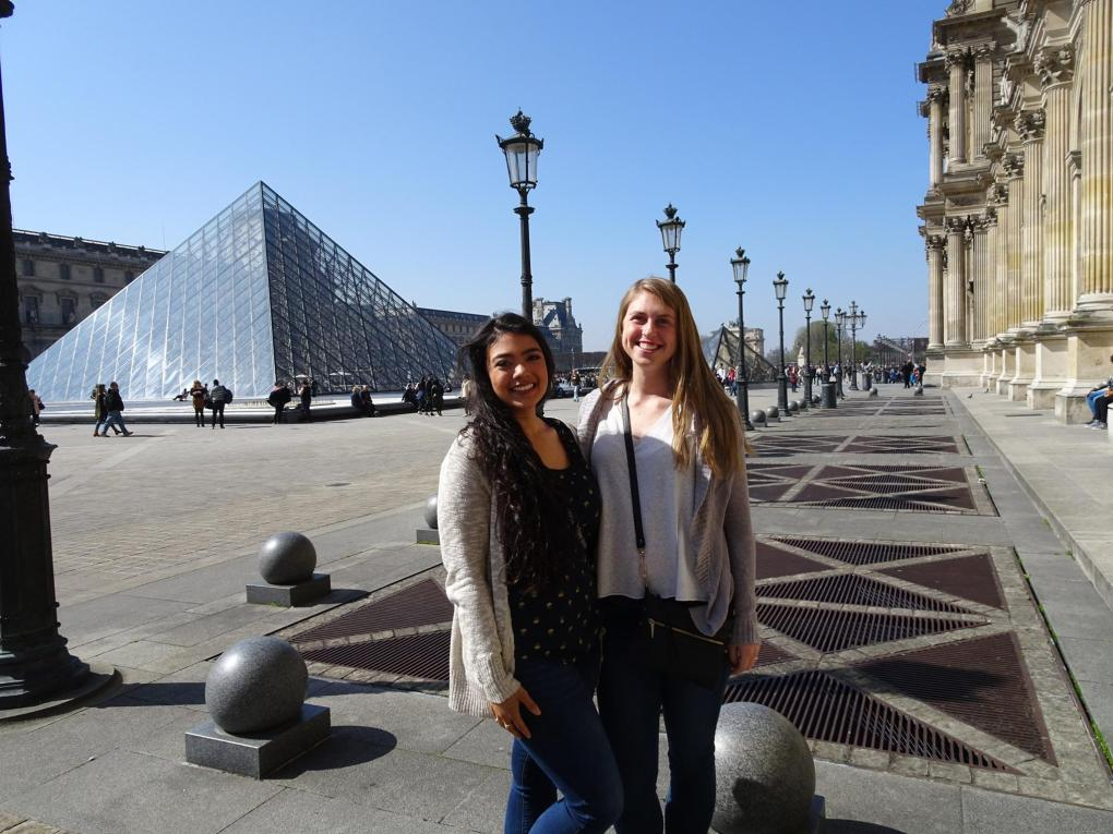 two girls standing in front of the Louvre museum in Paris