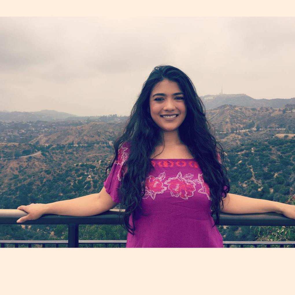 girl standing in front of the Hollywood Sign at Griffith Observatory, L.A.