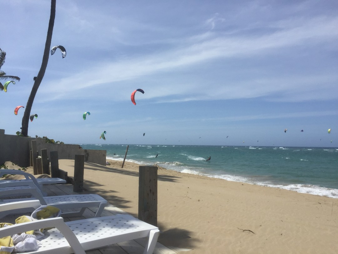 sand and ocean and blue sky with kite surfers