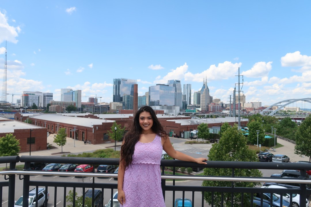 girl standing in front of Downtown Nashville skyline