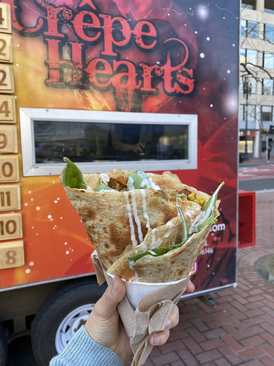 Vegan savory breakfast crêpe with Crêpe Hearts food truck in the background