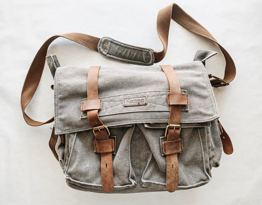 grey messenger bag with brown leather accents