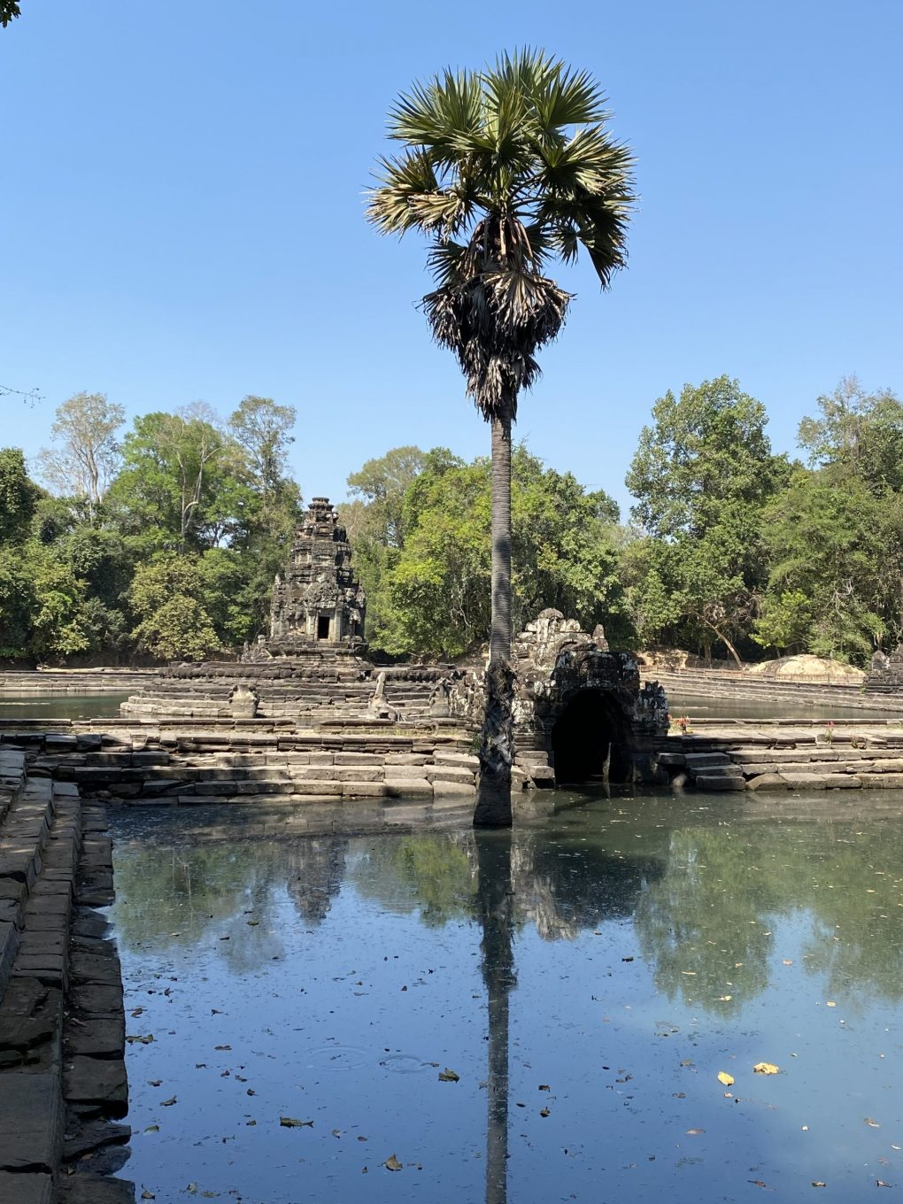temple in Angkor Archeological Park with aqueducts and palm trees