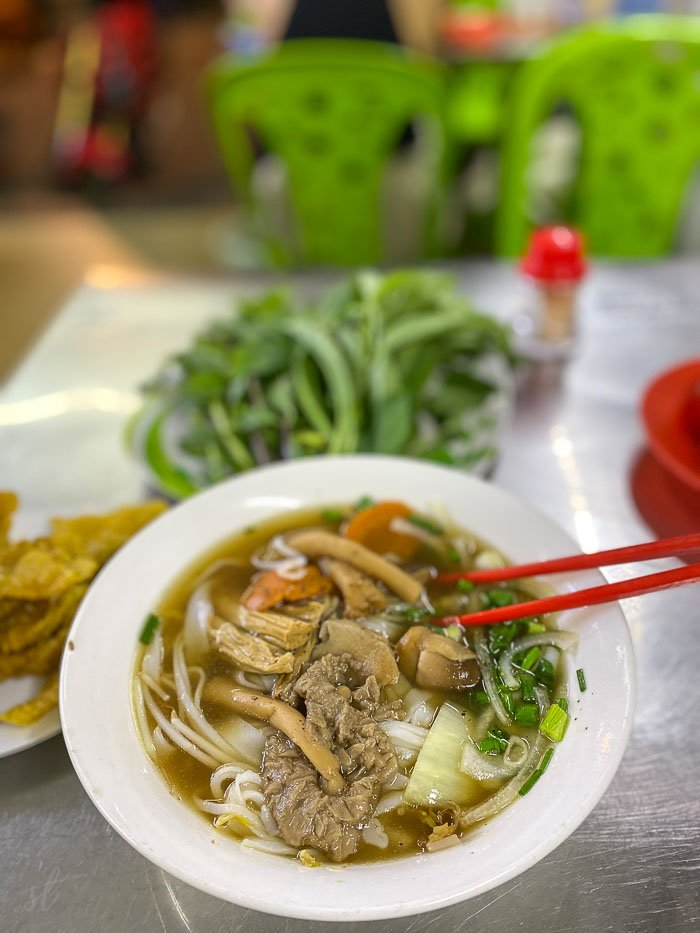 Bowl of vegan pho noodle soup with mushrooms, green onion, carrots, and broth